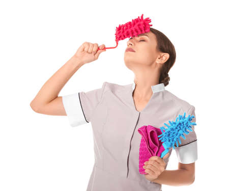 Tired chambermaid with cleaning supplies on white background