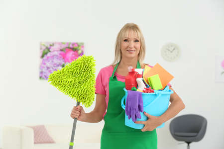 Mature woman with cleaning supplies at home