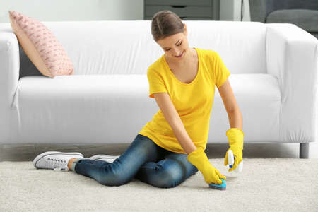 Young woman cleaning carpet at home