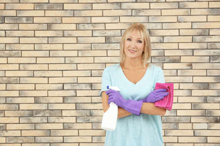 Mature woman with bottle  of detergent and rag against brick wall