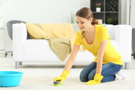Young woman cleaning carpet at home Stock Photo