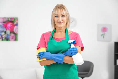 Mature woman with bottle of detergent and sponge at home