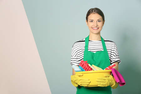 Woman with cleaning supplies on color background