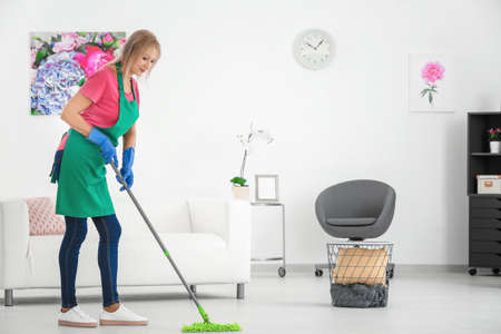 Mature woman mopping floor at home