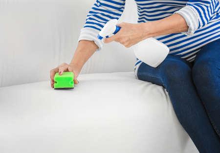 Woman cleaning sofa at home, closeup