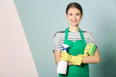Woman with bottle of detergent and sponge on color background