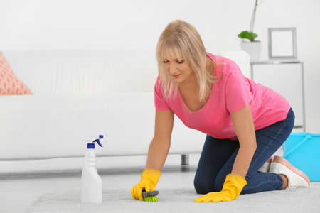 Mature woman cleaning carpet at home Stock Photo
