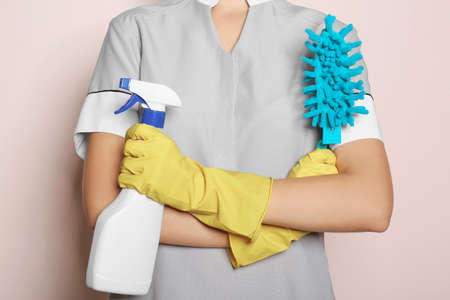 Woman with bottle of detergent and brush on color background, closeup