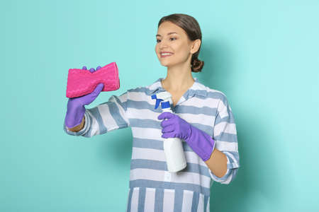 Woman with bottle of detergent and rag on color background