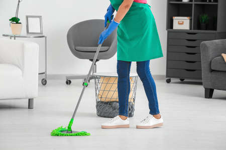 Woman mopping floor at home Фото со стока