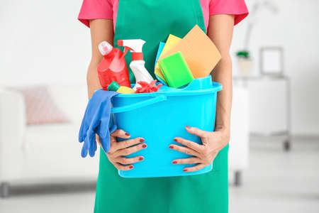 Woman with cleaning supplies at home, closeup