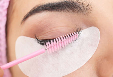 Young woman undergoing eyelash extensions procedure, closeup Stock Photo