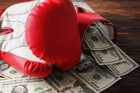 Boxing gloves and money on wooden background Stock Photo
