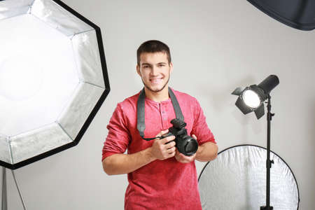 Young photographer in professional studio