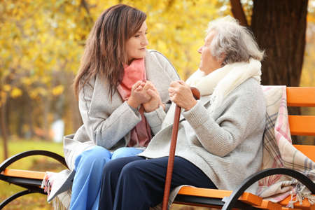 Senior woman with cane and young caregiver sitting on bench in park