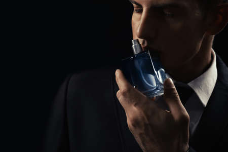 Handsome man with bottle of perfume on dark background, closeup