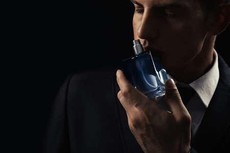 Przystojny mężczyzna z butelką perfum na ciemnym tle, zbliżenie