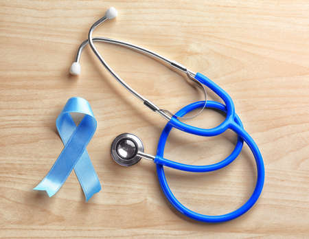 Blue ribbon and stethoscope on wooden background. Cancer awareness concept Stock Photo