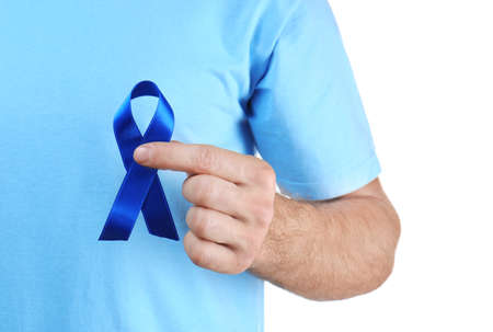 Young man holding blue ribbon on white background. Cancer concept