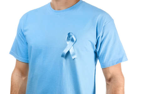 Young man in t-shirt with symbolic blue ribbon on white background. Cancer awareness concept Stock Photo