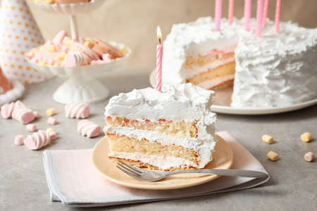 Piece of birthday cake with candle on table