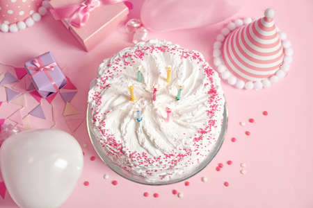 Birthday cake with candles on pink table