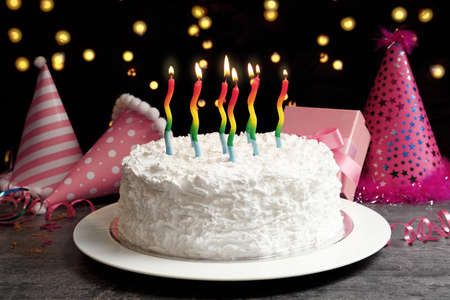 Dish with birthday cake and candles on table against lights background