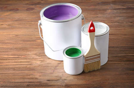 Multicolored paint in tin cans on wooden background Stock Photo