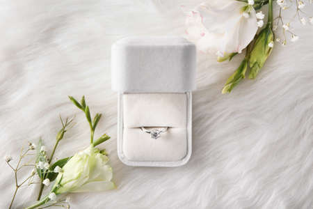 Box with luxury engagement ring on fur, top view 스톡 콘텐츠