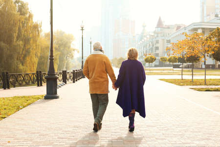 Elderly couple walking in the street on autumn day