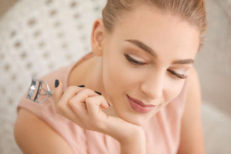 Beautiful young woman with eyelash curler at home