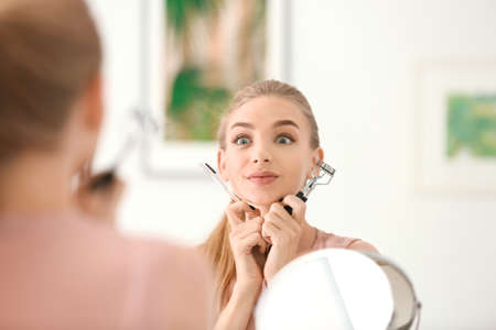 Emotional young woman with eyelash curler and comb at home
