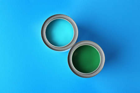 Tin cans with bright turquoise and green paint on color background, top view