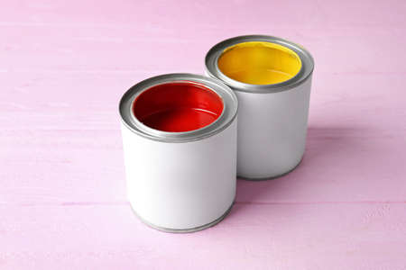 Tin cans with bright red and yellow paint on color background
