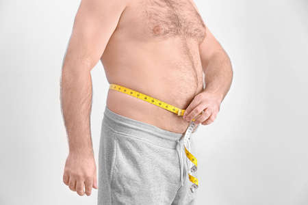 Overweight man with measuring tape on light background