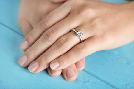Woman wearing luxury engagement ring on color background, closeup