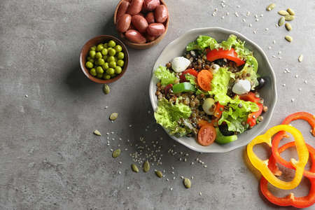 Bowl with delicious vegetables salad on grey background, top view Stock Photo