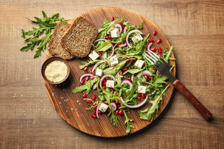 Wooden board with fresh tasty salad on table