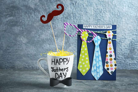 Cup with text HAPPY FATHERS DAY, decor and card on table