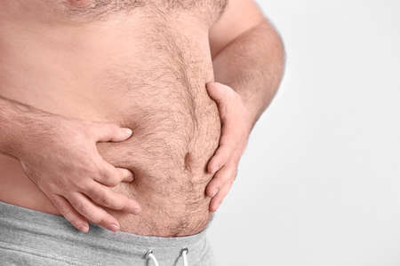 Overweight young man on light background Stock Photo