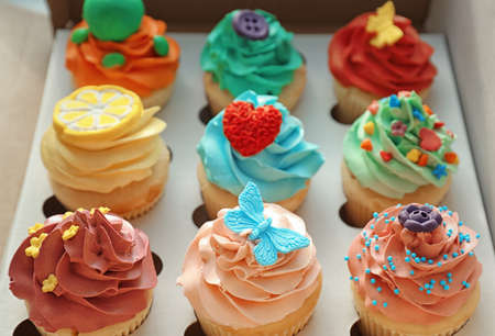 Tasty colorful cupcakes in open paper box Stock Photo