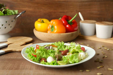 Plate with delicious vegetable salad on table