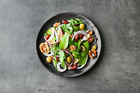 Plate with delicious vegetable salad on grey background