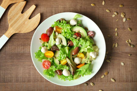 Plate with delicious vegetable salad on table, top view Stock Photo