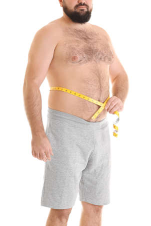 Overweight man in shorts with measuring tape on white background