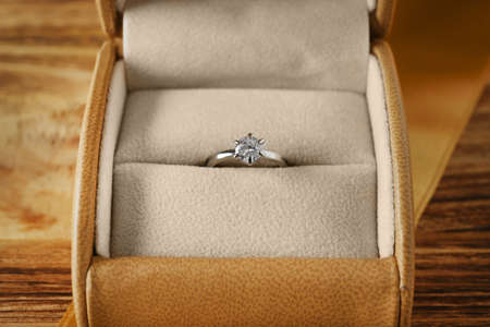 Box with luxury engagement ring on wooden background, closeup