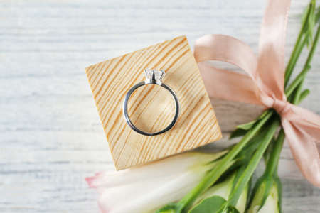 Wooden cube with luxury engagement ring on light background, top view