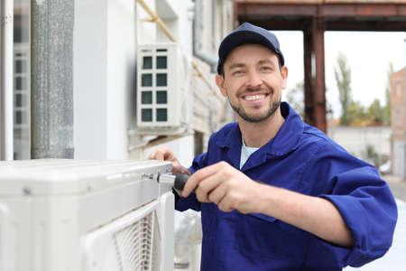 Mężczyzna technik naprawy klimatyzatora na zewnątrz