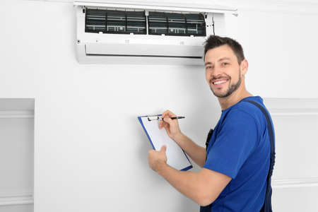 Male technician checking air conditioner indoors 版權商用圖片