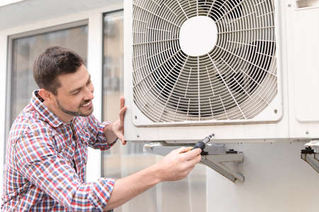 Handsome man repairing air conditioner outdoors